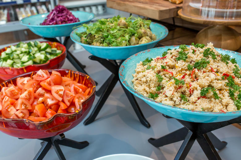 Photo of assorted salads in large coloured bowls