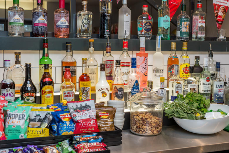 Photo of the top of a bar, with various alcoholic spirits, crisps, nuts and other snacks neatly arranged