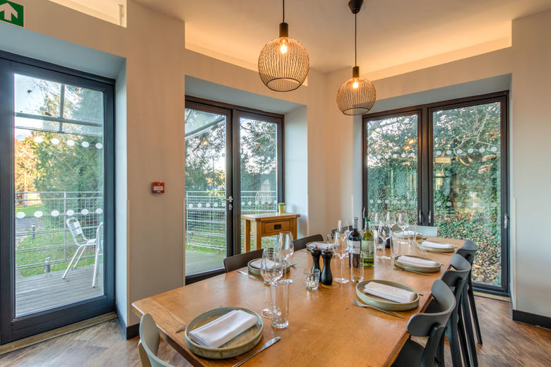 Photo of a large dining table with 8 chairs, set for dinner with crockery, cutlery and glasses and surrounded by large windows