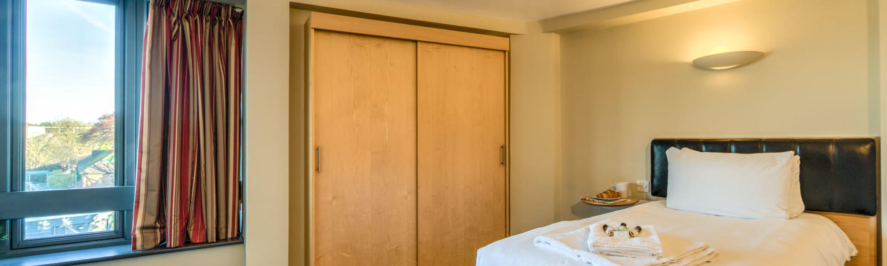 Photo of a hotel room with single bed, wardrobe and window