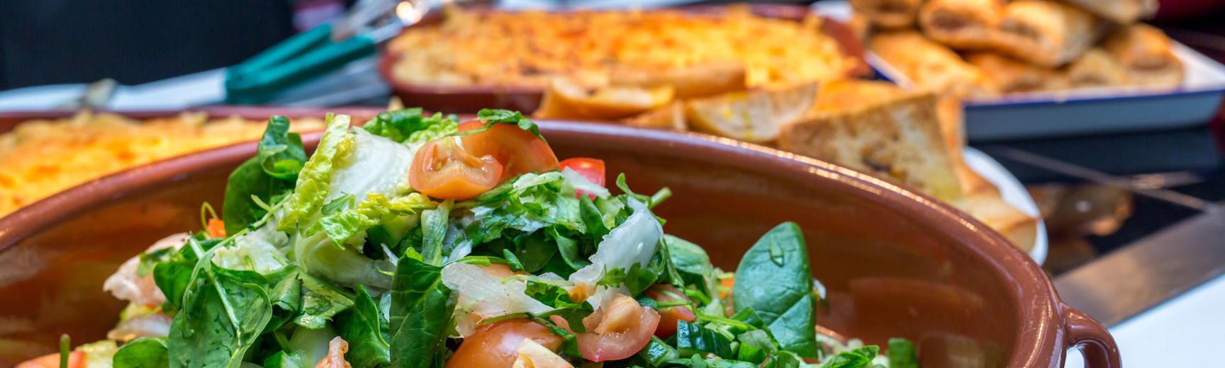 Close-up photo of a bowl of green salad with various hot food in background
