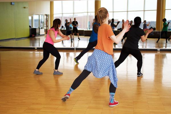 Photo of women dressed in gym-wear dancing in a fitness studio