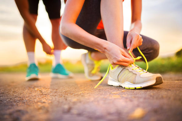 Close up photo of a runner lacing up their trainers