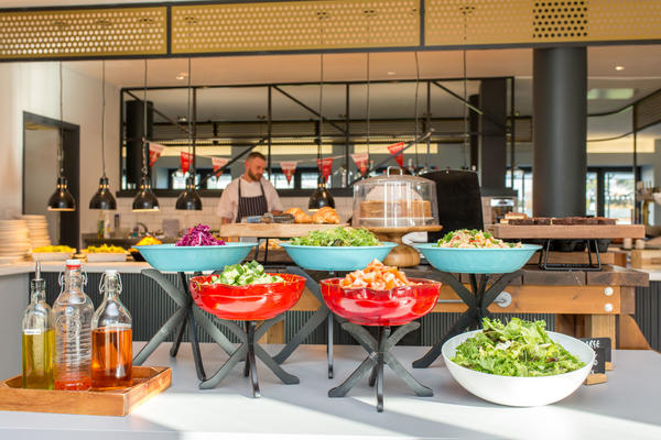 Photo of a cafe with salad bar in the foreground, and cakes, pastries and hot food in the background