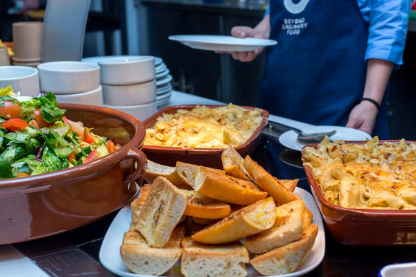 Photo of serving bowls of pasta, bread and salad on a hot plate, ready to be served