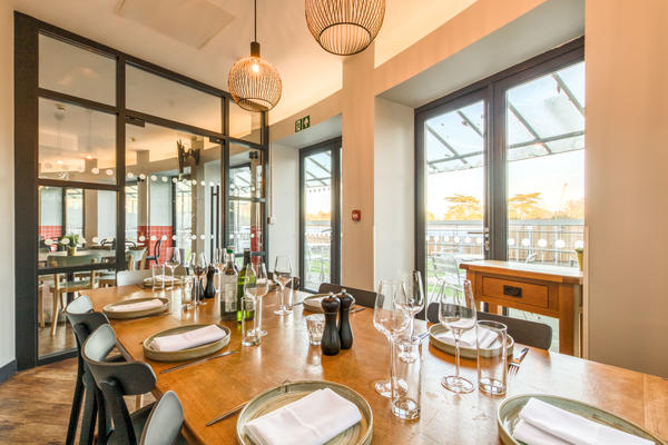 Photo of a large dining table set for dinner with crockery, cutlery and glasses and surrounded by large windows looking out into the cafe area