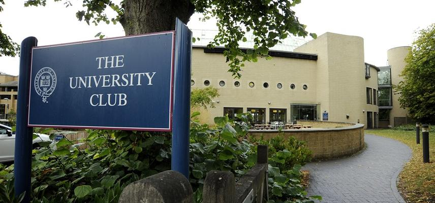 Photo of a blue sign reading 'The University Club' in white text, outside the front of the Club